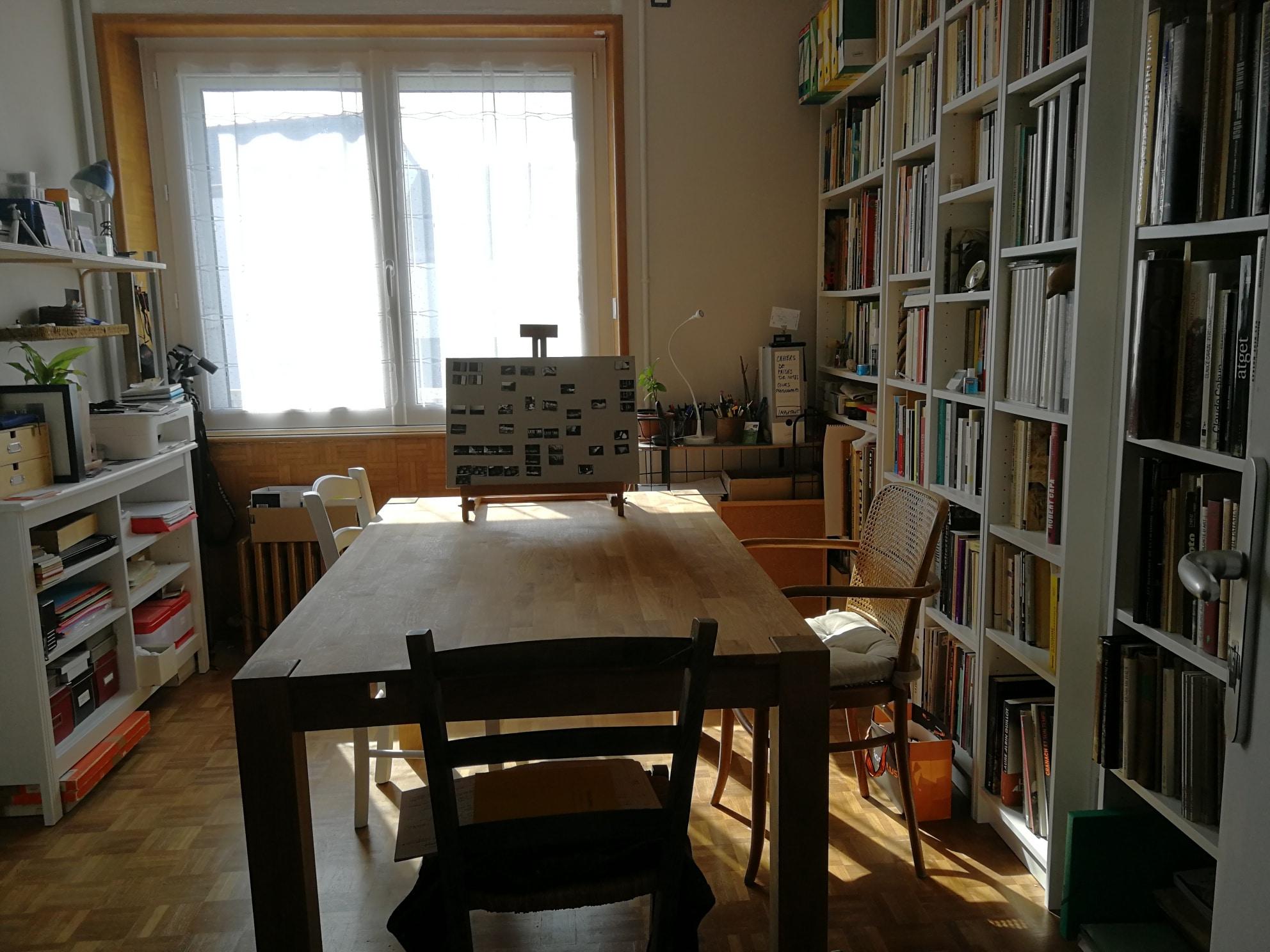 Les yeux de l'imaginaire. La salle de cours avec sa grande bibliothèque de livres photos et la table de travail.
